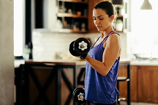 Woman lifting dumbbells at home