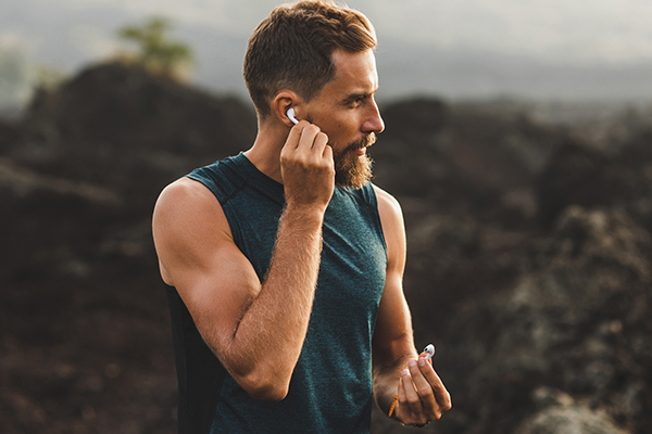Man using wireless earphones air pods on running outdoors.