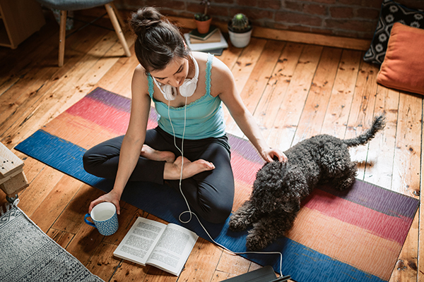 Woman sitting on yoga mat with dog