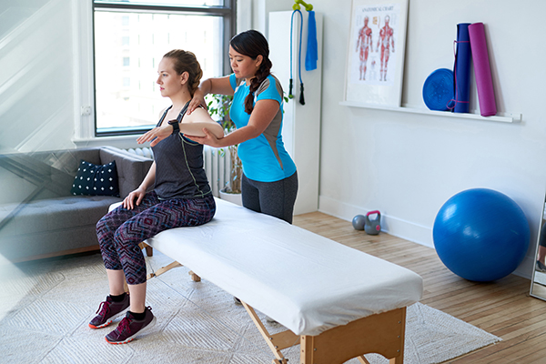 Woman with shoulder injury working with physical therapist
