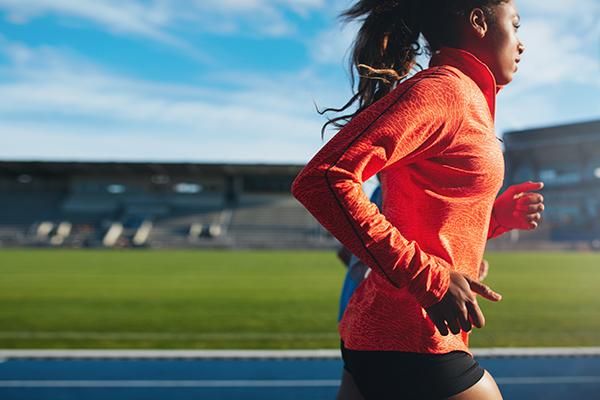 Female athlete training on race track