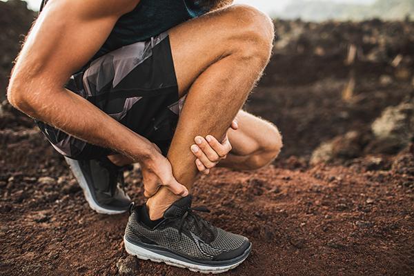 Man grabbing Achilles tendon