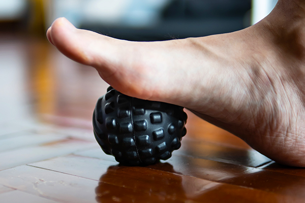 Foot on massage ball to relieve Plantar fasciitis or heel pain.