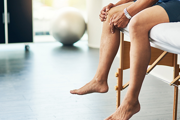 Man gripping knee
