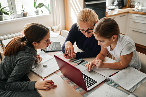 Mom helping daughters with remote learning