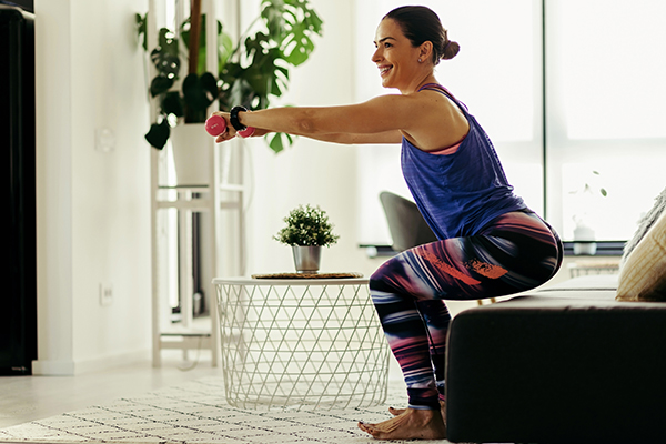 Woman exercising at home doing lunges exercise.