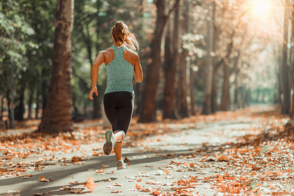 Woman Jogging Outdoors In Autumn