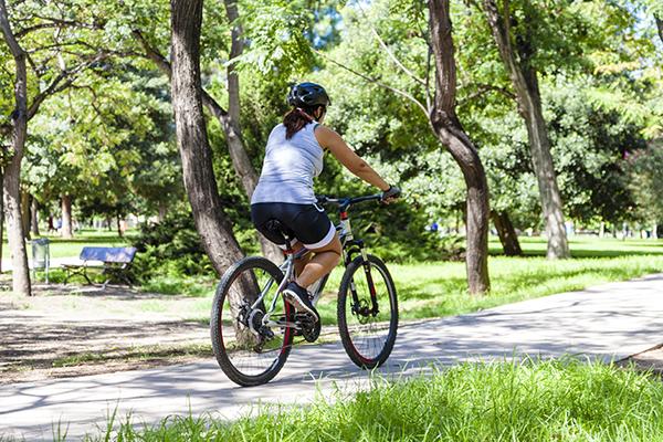 Woman biking through a park