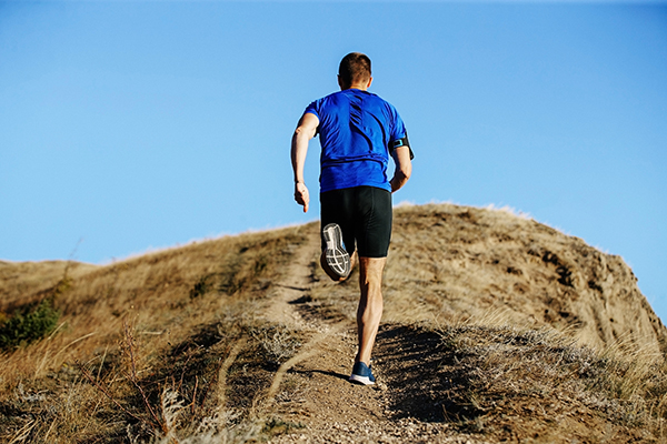 Back view of man running up hill