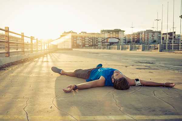 male runner lying on the ground exhausted