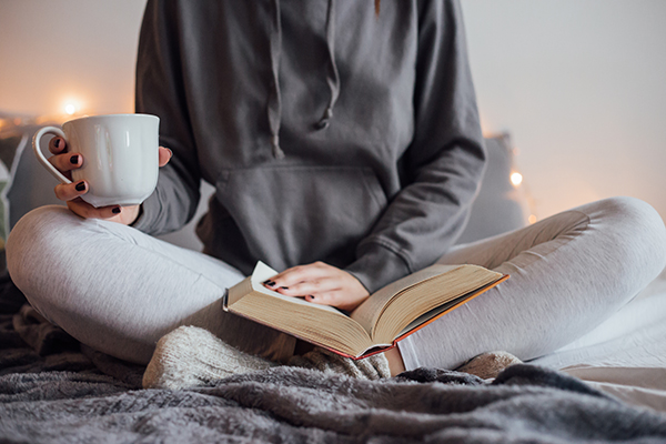 Girl holding cup of hot tea and reading in bed.