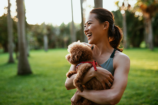 Woman holding dog, laughing