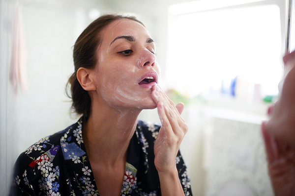 Woman using cleanser on her face at home