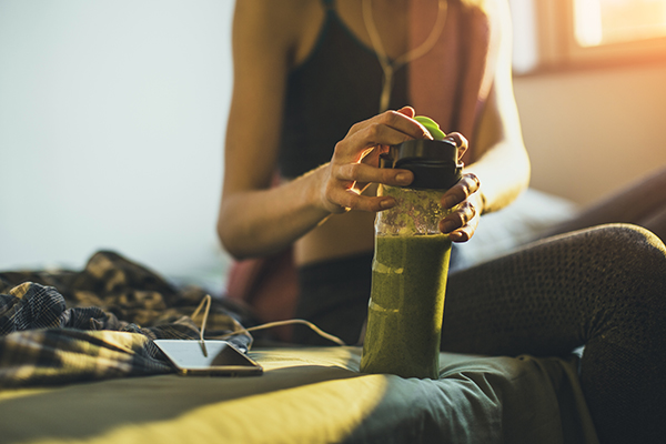 Woman drinking smoothie after a run