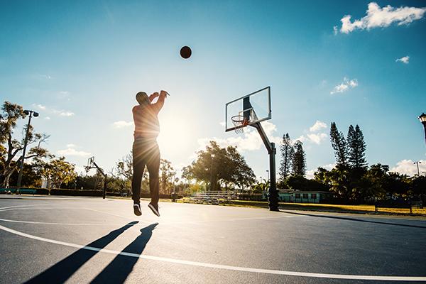 Man shooting basketball hoops outside