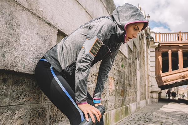 Exhausted runner resting against a wall