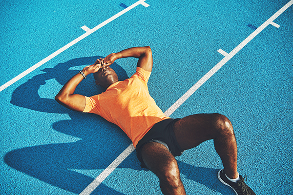 Exhausted young man lying down on running track