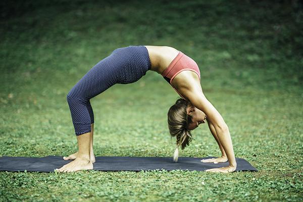Young woman doing yoga, wheel pose or Urdhva Dhanurasana