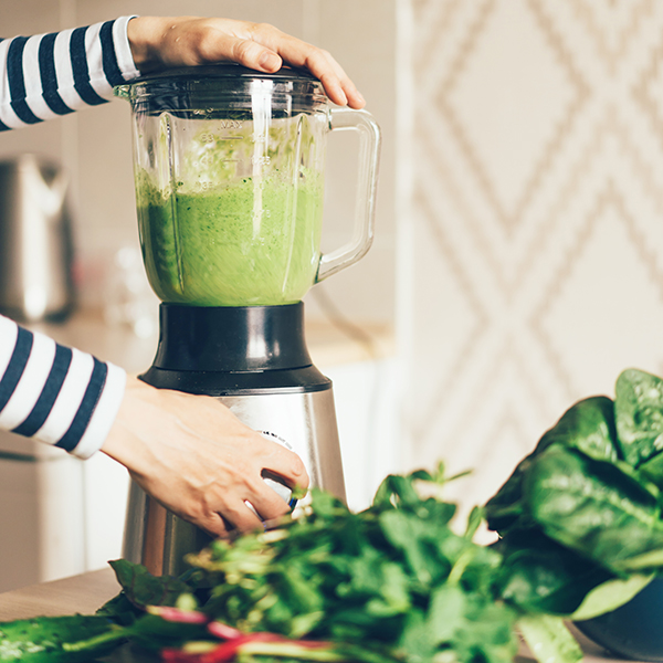 Woman making a green smoothie