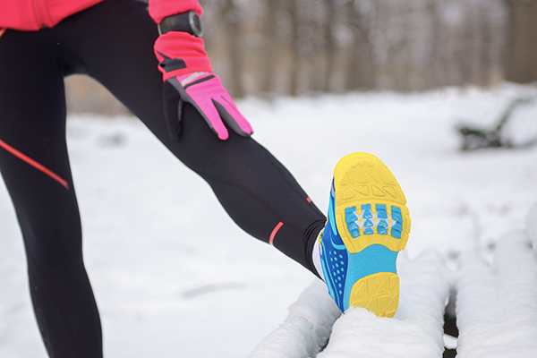 Runner stretching leg on snowy bench