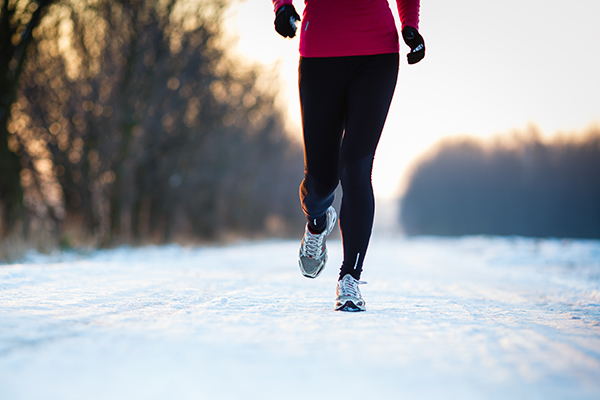 Shot of lower legs of runner jogging on snowy road