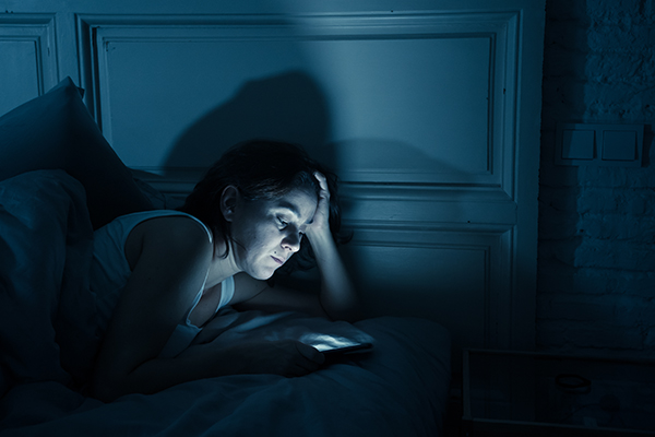 Woman checking smartphone in bed