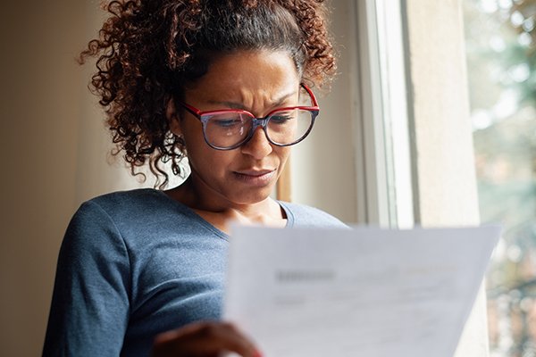 Worried woman looking at piece of paper