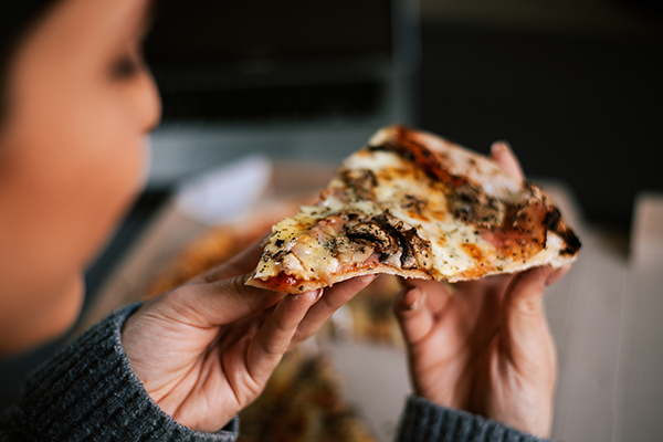 Woman eating slice of pizza