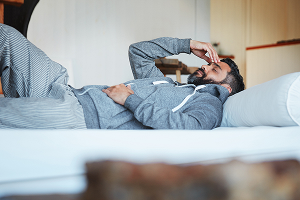 man lying on his bed feeling exhausted.