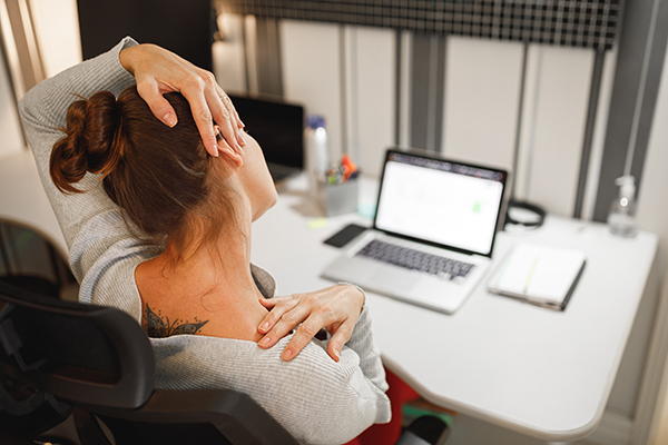 Woman stretching her neck while working at home