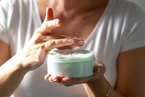 Woman holding jar of aloe vera lotion