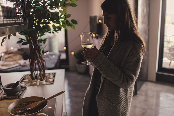 Woman drinking wine at home alone