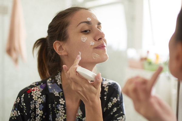 Woman applying face cream in bathroom