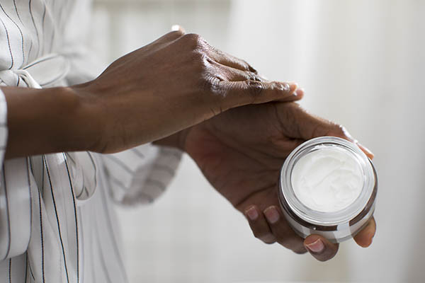woman putting lotion on hand