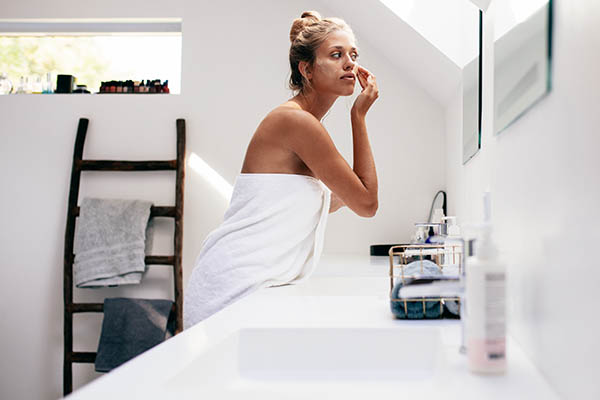 Woman applying facial lotion in front of bathroom mirror