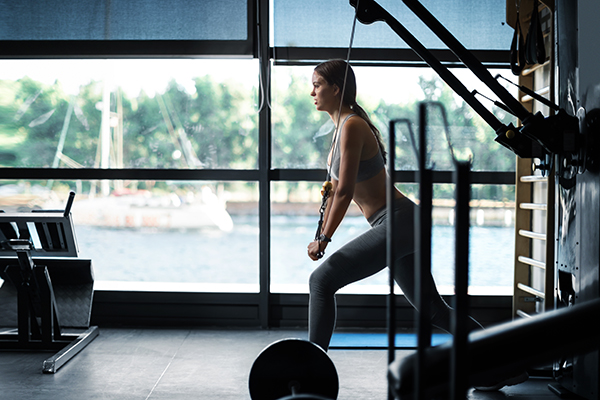 Woman using cable pulley machine at a gym