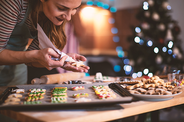 woman decorating holiday cookies