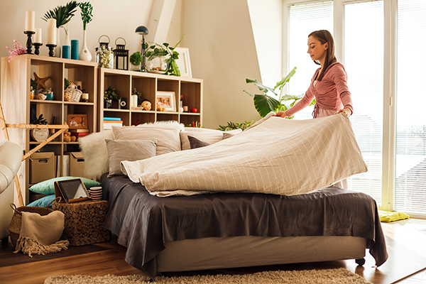 Woman making her bed at home