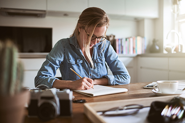 Woman writing in a journal at home