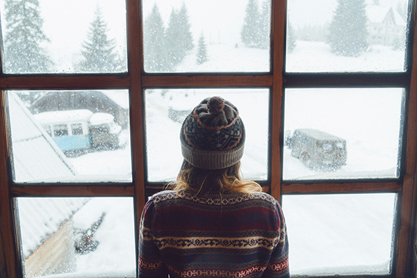 Woman looking out window at winter landscape