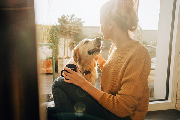 Woman having coffee alone with dog