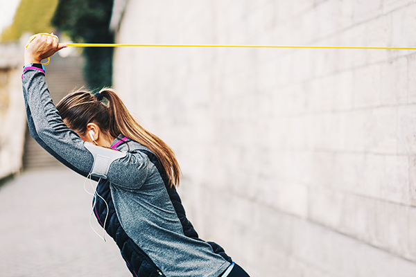 Woman using resistance band anchored to wall