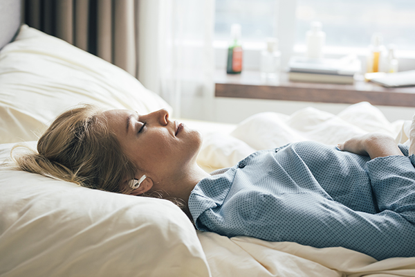 Woman doing guided sleep meditation in bed