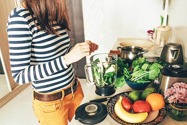 Woman in her kitchen preparing a smoothie.