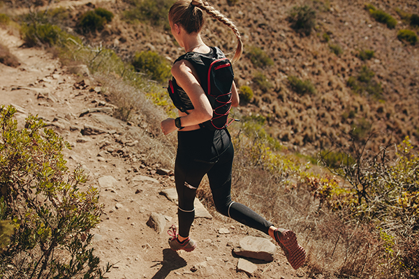 Woman running trail with hydration running vest