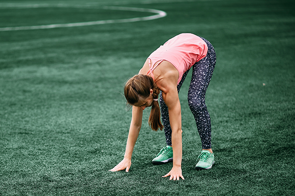 Woman doing burpees on grass field