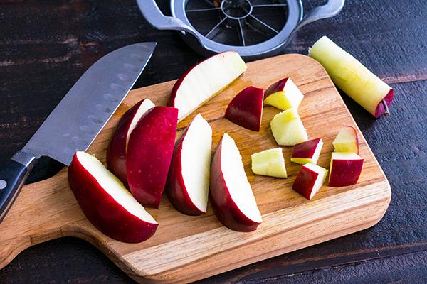 Cortar una manzana roja en pedazos sobre una tabla de cortar de madera