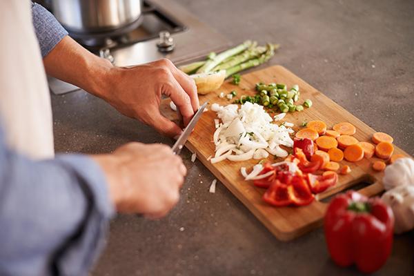 El hombre corta las verduras en una tabla de cortar de madera