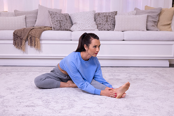 Autumn Calabrese stretching her legs at home