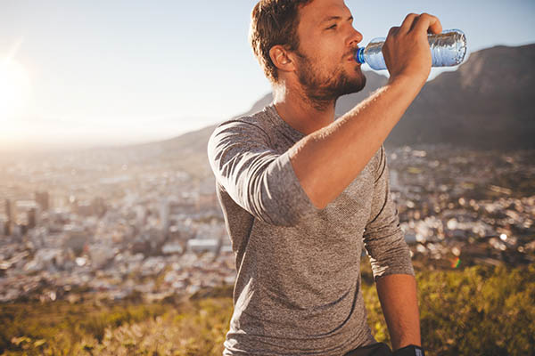 Man drinking water outside